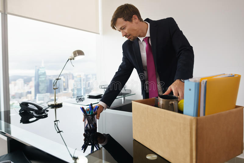 Just Hired Business Man In New Office Putting Desk In Order. Businessman recently hired for corporate job moves into his new executive office with a view of the stock photography