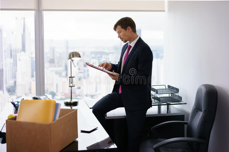 Just Hired Manager Business Man Moves To New Office. Businessman recently hired for corporate job moves into his new office. He takes out a folder from a box and stock image
