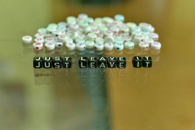 JUST LEAVE IT  written with Acrylic Black cube with white Alphabet Beads on the Glass Background.  stock photos