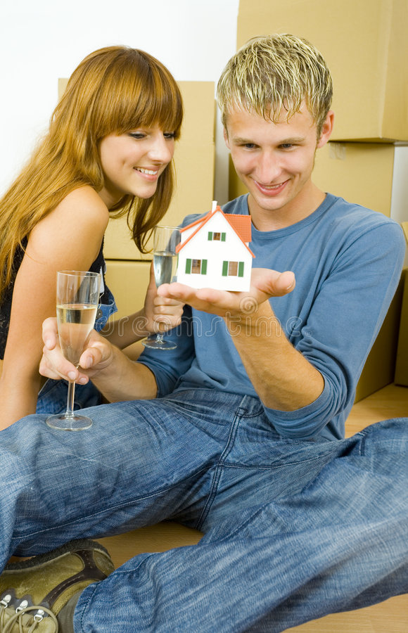Just like real. Young couple sitting on the floor in flat. They're looking happy. Man is holding house miniature and they're looking at it stock photos