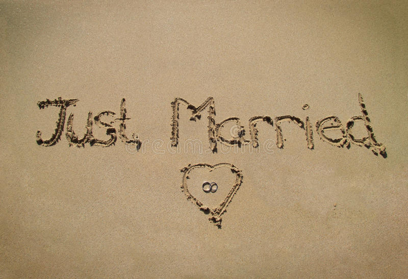 Just married. Written in the sand with rings royalty free stock photos