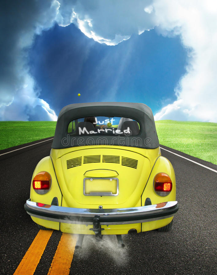 Just married. A yellow convertible volkswagen beetle with Just Married on the window. The car is traveling down an asphalt road into a heart shaped sky. One half stock images