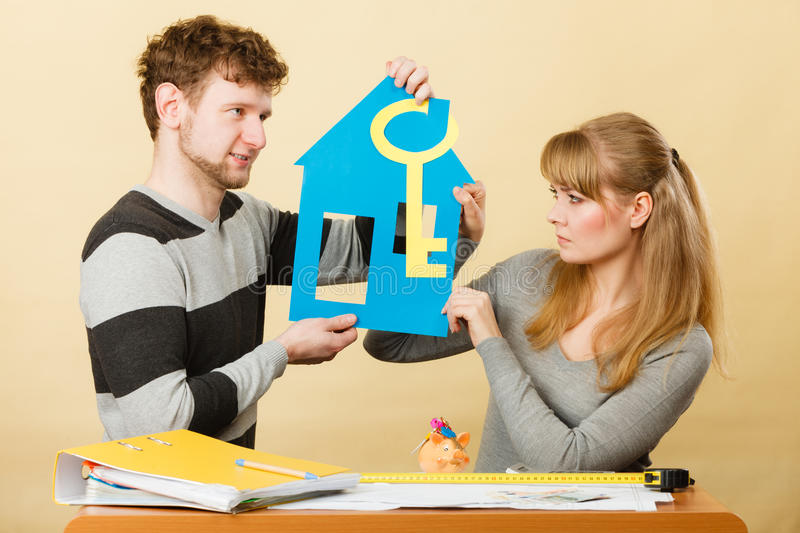 Just married arguing about future. Real estate ownership finance concept. Young couple arguing about future. Man and women holding house key cutout discussing stock photos
