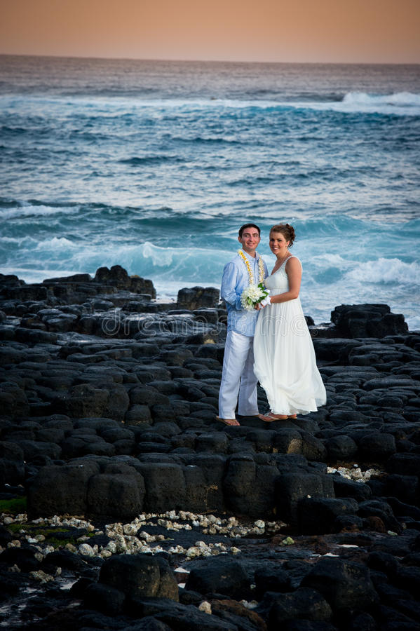 Just Married. Beautiful couple on rocky shore. stock photo