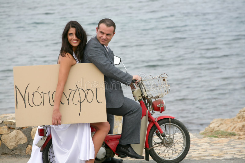 Just Married - bride and groom on aged motorcycle. Beautiful bride and groom eloping on aged motorcycle stock photos