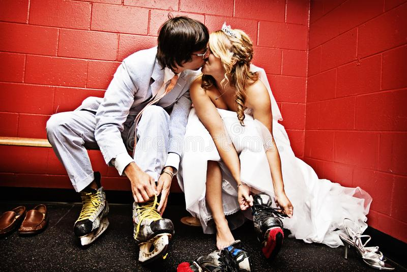 Bride and Groom putting on ice skates. A just married bride and groom kissing while lacing up ice hockey skates in an ice rink royalty free stock images