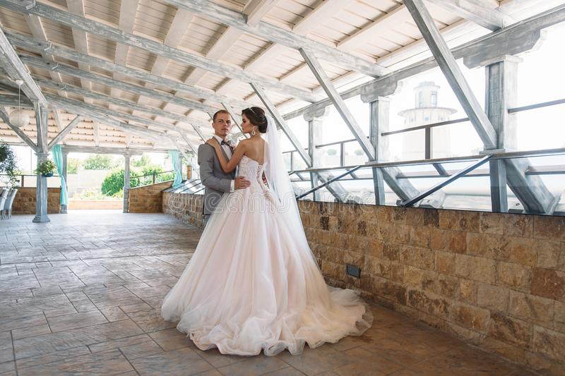 Just married couple of beautiful groom in a gray business suit and a bride in a luxurious white dress with a veil with. Amazing haircut. Newlyweds at wedding stock images