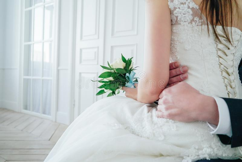 Just married couple with bouquet of white roses in studio, wedding details close up stock image