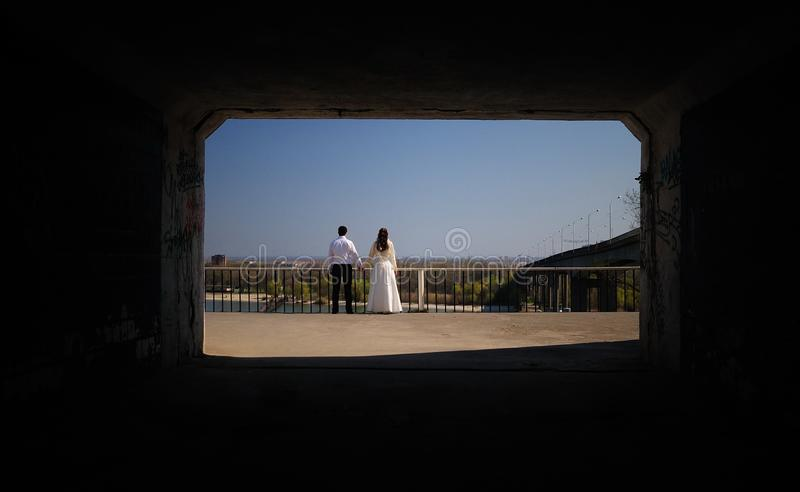Just-married couple in the end of a tunnel