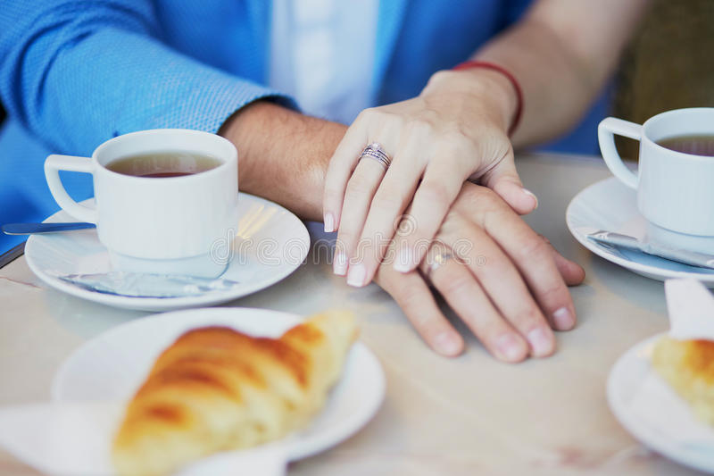 Just married couple holding hands in Parisian cafe. On their wedding day. Focus on bride ring royalty free stock photos