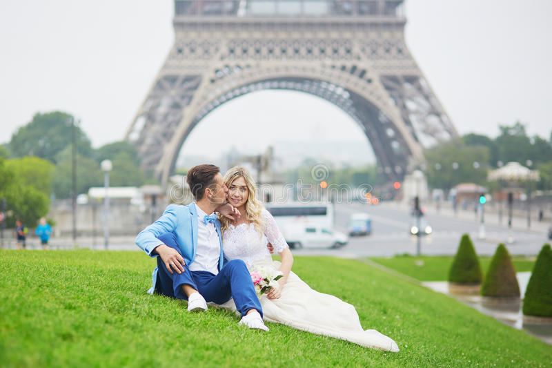 Just married couple near the Eiffel tower in Paris. Just married couple near the Eiffel tower on their wedding day. Bride and groom in Paris, France royalty free stock image
