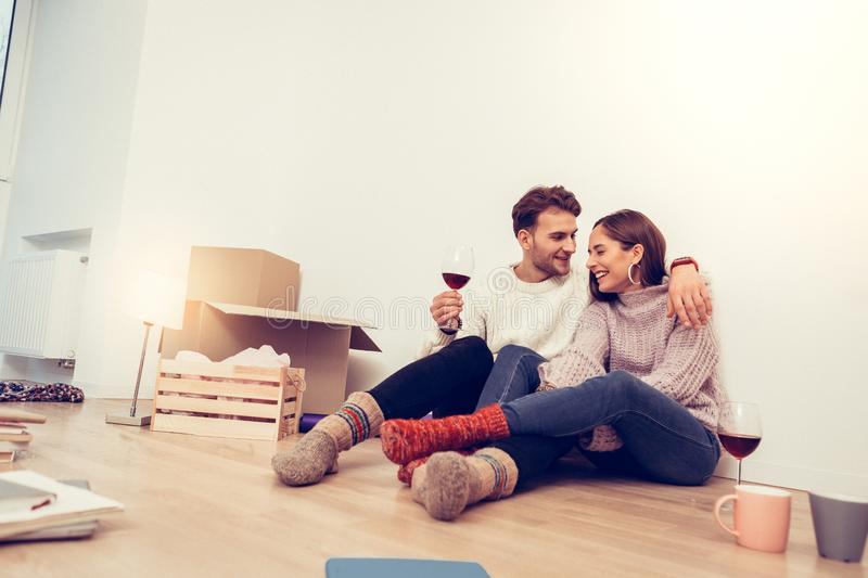 Just married couple spending their first evening in new house. First evening. Just married couple spending their first evening in new house drinking wine sitting stock images