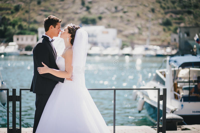 Just married couple walking in small cove. Just married bride and groom walking in small cove royalty free stock images