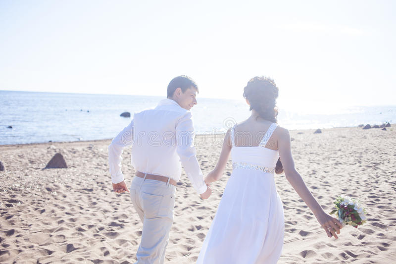 Just married happy couple running on a sandy beach. Just married couple running on a sandy beach royalty free stock image
