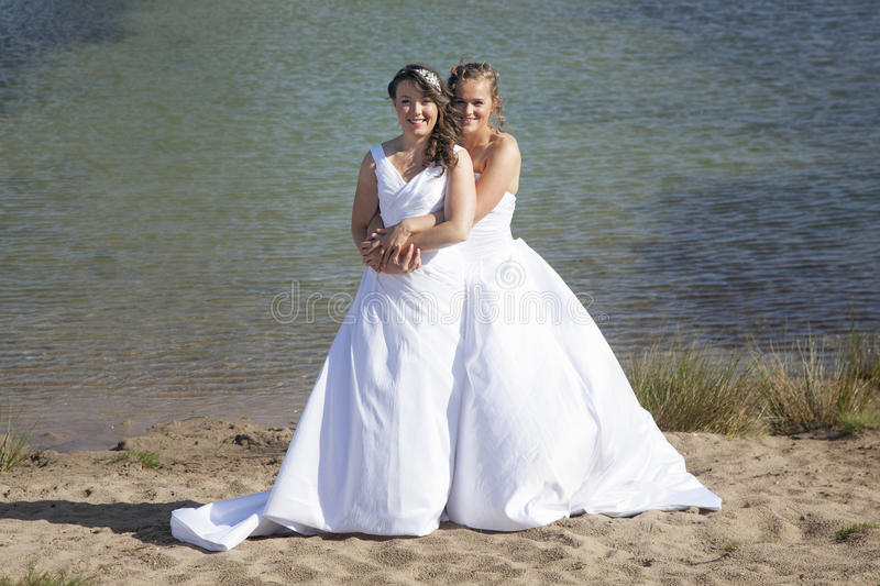 Just married happy lesbian couple in white dress embrace near sm. All lake and forest on sunny day stock photography