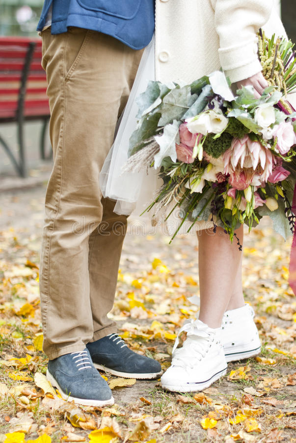 Just married loving hipster couple in wedding dress and suit outdoor in city setting stock image