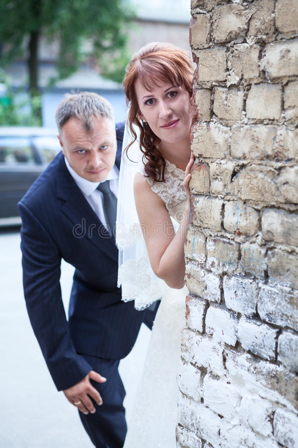 Just married people peek around corner of brick wall. Just married people peek around the corner of brick wall stock photo