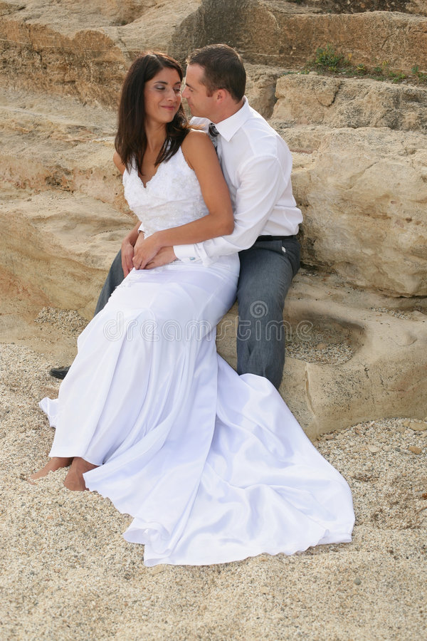 Just Married - smiling bride and groom. Smiling bride and groom on the rocks royalty free stock images