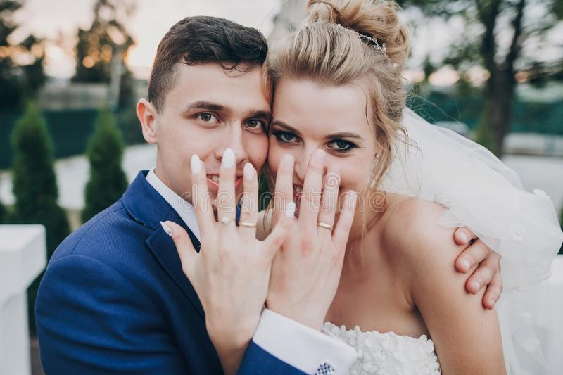 Just married. Stylish happy bride and groom showing hands with wedding rings at wedding reception outdoors. Gorgeous wedding stock image