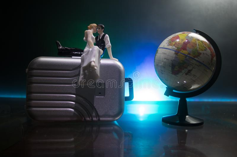 Just married travel concept. Artwork table decoration with couple near suitcases ready to honeymoon. Dark blue background. Selective focus stock photography