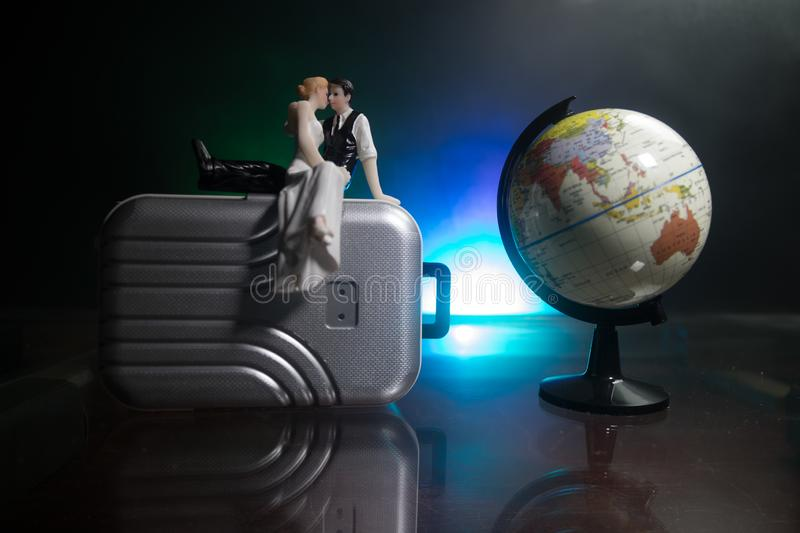 Just married travel concept. Artwork table decoration with couple near suitcases ready to honeymoon. Dark blue background. Selective focus stock photos