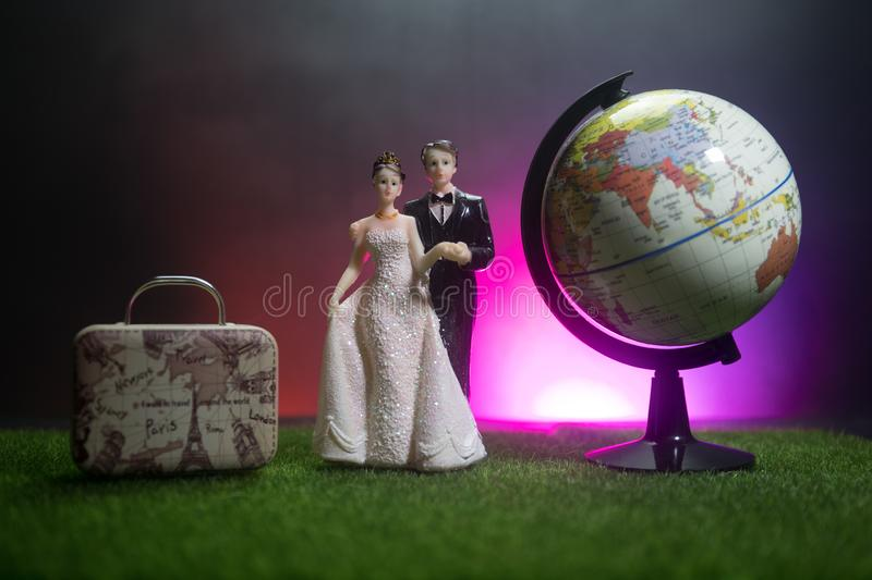 Just married travel concept. Artwork table decoration with couple near suitcases ready to honeymoon. Dark blue background. Selective focus stock image