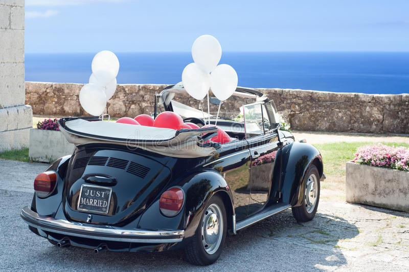 Just married. Vintage wedding convertible car with just married sign and balloons attached waiting for newlywed couple. Horizontal shoot stock photos