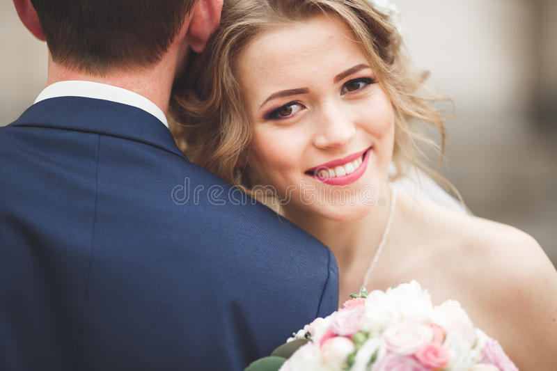 Just married wedding couple posing and bride holding in hands bouquet.  royalty free stock photo