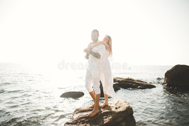 Just married wedding couple walking on the beach at sunset. Just married couple on walking on the beach at sunset stock image