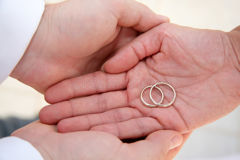 Just Married - wedding rings. Bride and groom's palms holding wedding rings stock photo