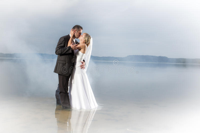 Just married young couple in a misty lake royalty free stock photos