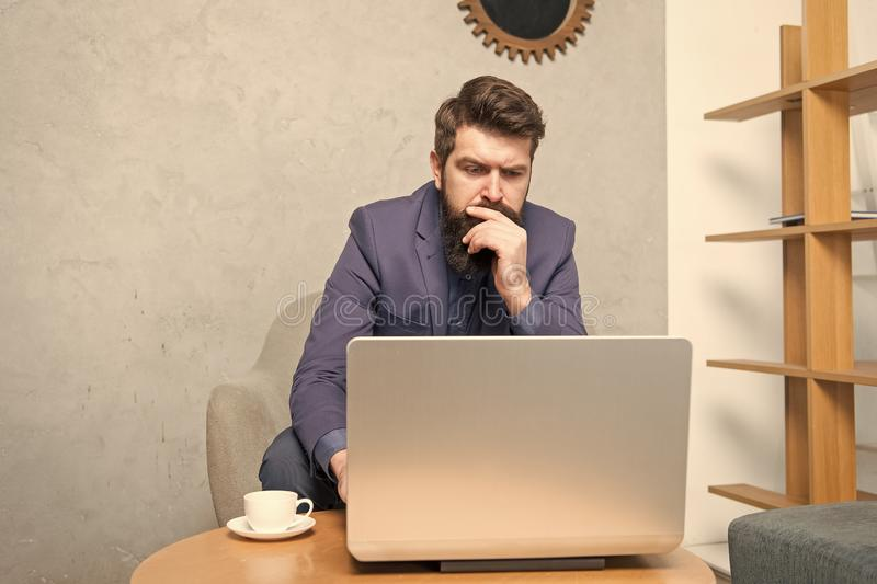 Just me, my computer and a cup of coffee. Professional computer repairman or tech worker. Bearded man working at laptop royalty free stock photo