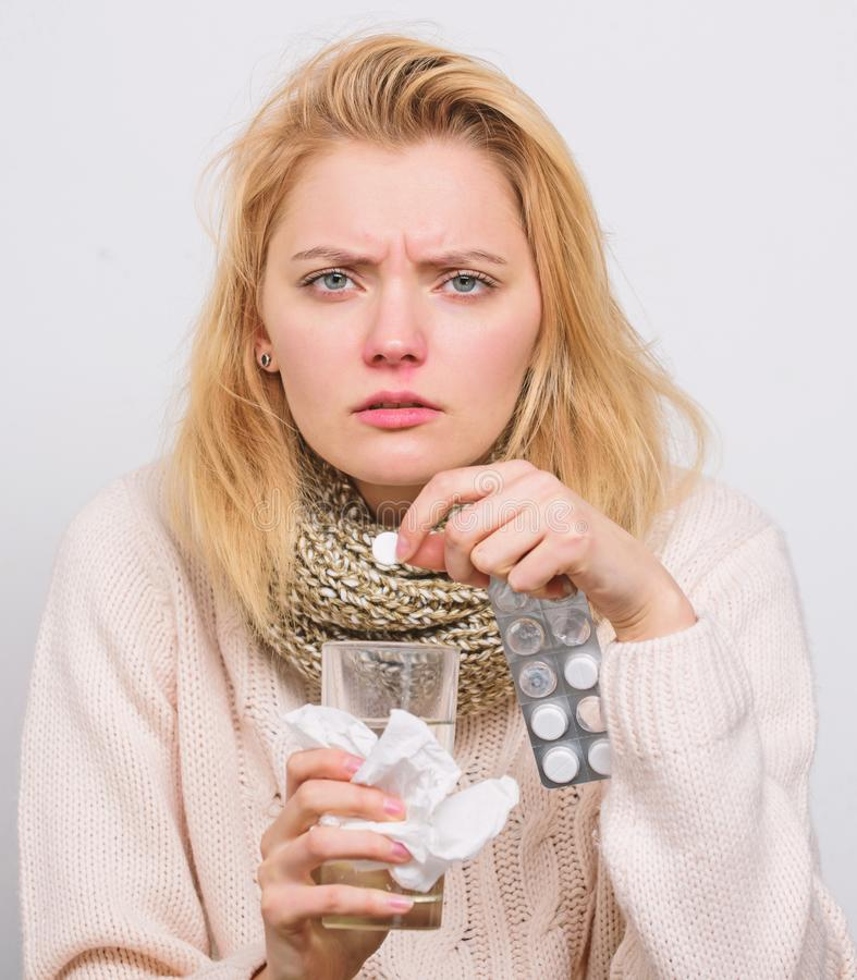 Just a pill can help. Unhealthy woman holding pills and water glass. Ill woman treating symptoms caused by cold or flu. Cute sick girl taking anti cold pills stock image