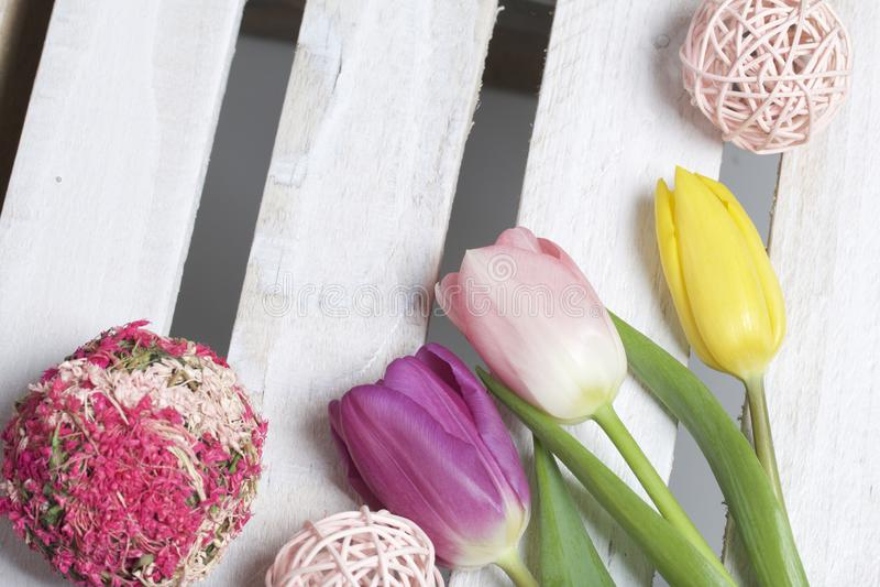 just rained Букет тюльпанов других цветов на предпосылке деревянных доск Около декоративных плетеных шариков стоковые фотографии rf