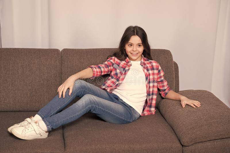 Just relaxing here. Feel comfortable on this couch. Kid girl with long hair relaxing. Favorite place for relaxing at. Home. Cozy home atmosphere. Carefree royalty free stock photography