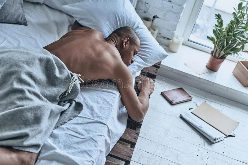 Just resting. Top view of young African man sleeping while lying royalty free stock image