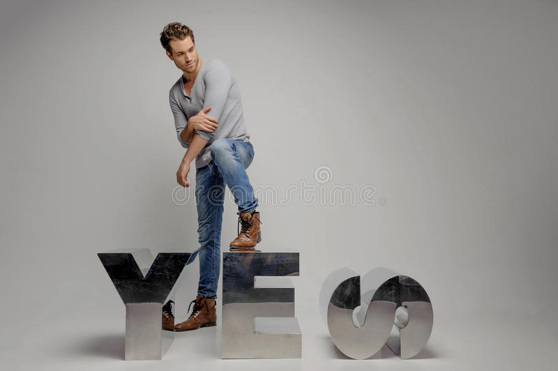 Just say �es� Handsome young men stepping on the metal letter and looking away while isolated on grey royalty free stock photo