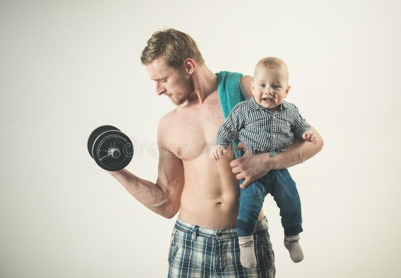 Just sport. Strong man with dumbbells hold baby boy. Father build biceps triceps with son. Father and child training. Just sport. Strong men with dumbbells hold stock image