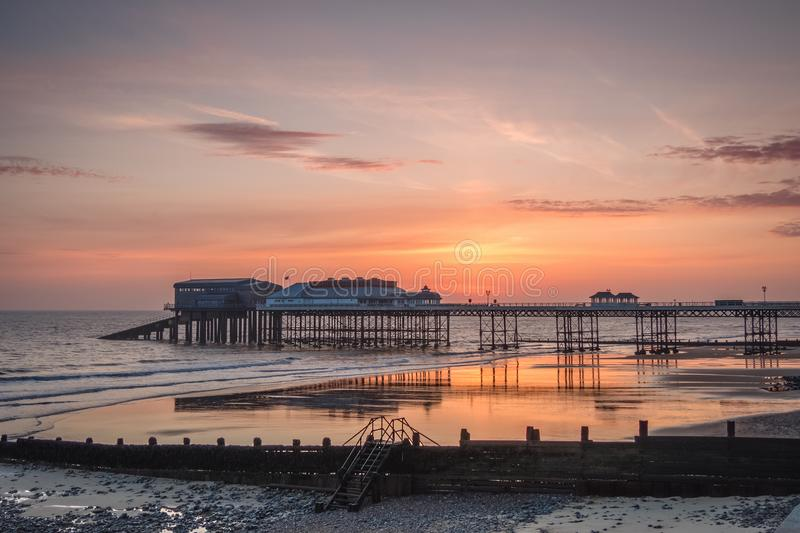 A New Day at Cromer Pier. Just before sunrise and the sky is lighting up. Dramatic skies over the pier as the sun nears the horizon. Taken first week of April royalty free stock photography