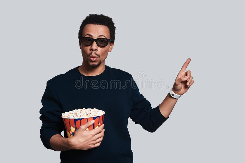 Just take a look!. Handsome young man in casual clothing looking at camera and pointing copy space while standing against grey background stock image