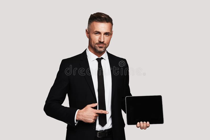 Just take a look!. Handsome young man in full suit pointing copy space on digital tablet and smiling while standing against grey background royalty free stock photos