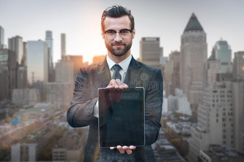 Just take a look! Portrait of cheerful young man in suit showing digital tablet at camera while standing against of stock photo