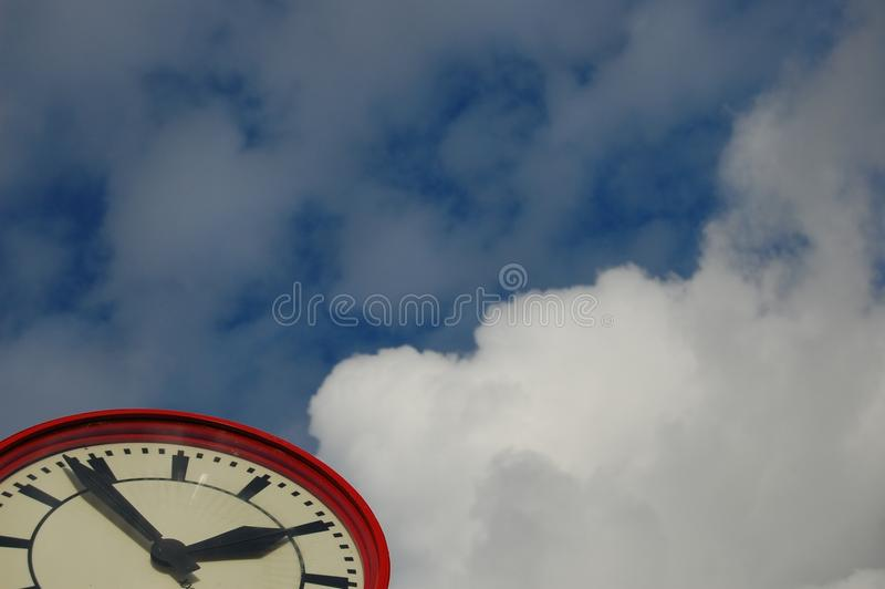 Just in time clock. The time with a blue sky background stock image