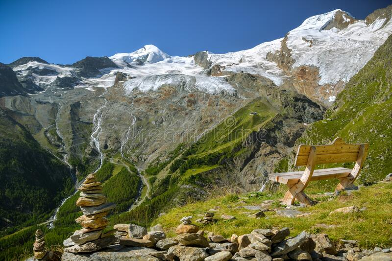 Just to sit and relax looking at majestic Fee Glacier located above Saas-Fee village. In Swiss Alps stock image