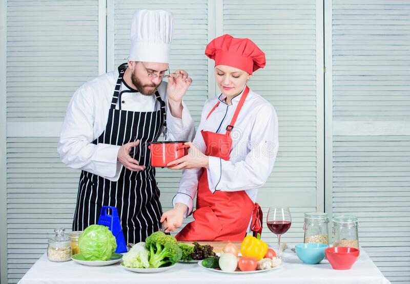 Just try this. Woman and bearded man cooking together. Try ingredients before cook. Estimate taste. Healthy food stock photo