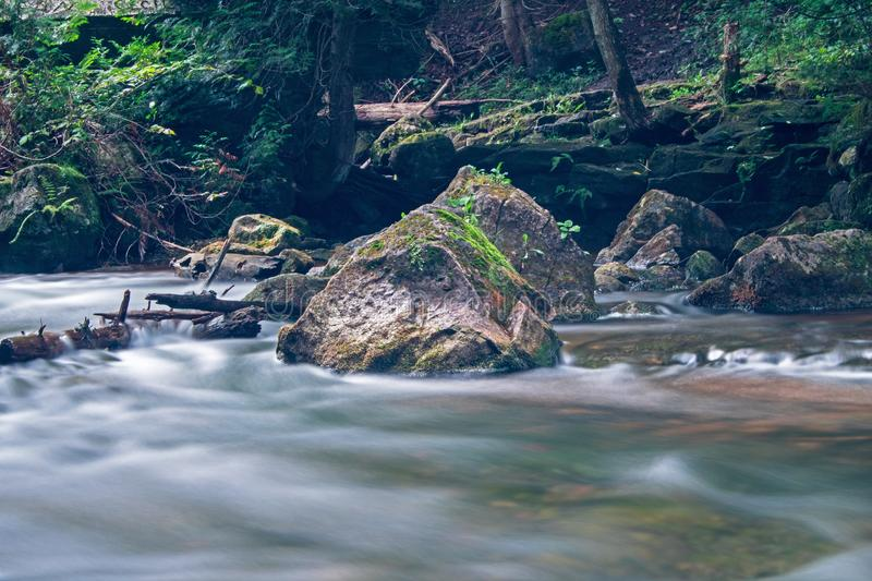 Just Upstream From Hoggs Falls On The Boyne River. A moss covered rock sits solid in the fast moving waters of the Boyne River, just upstream from Hoggs Falls royalty free stock photos