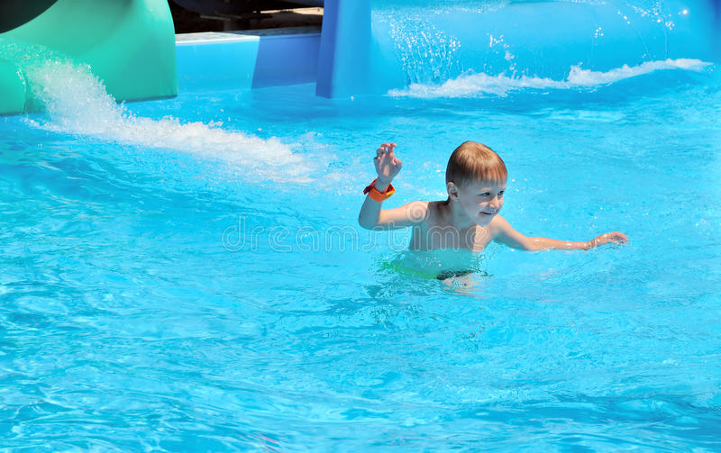Just from the water slide. Funny boy caming out of water after the water slide stock image