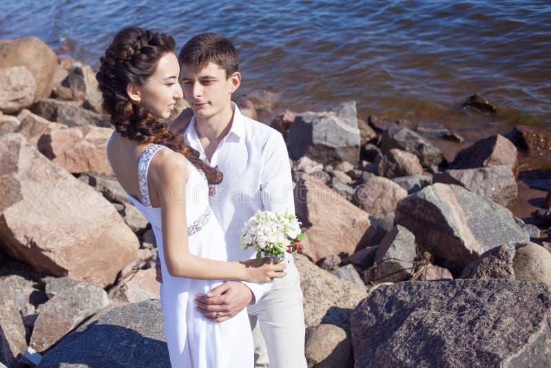 Juste couples heureux mariés sur une plage rocheuse images stock