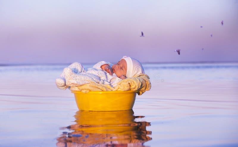 Juste le bébé dans un panier nage dans l'eau photographie stock
