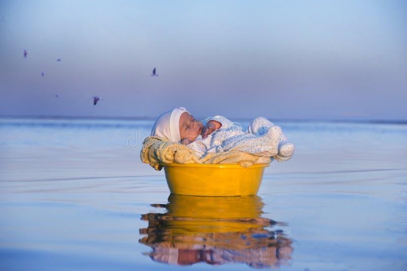 Juste le bébé dans un panier nage dans l'eau photo stock